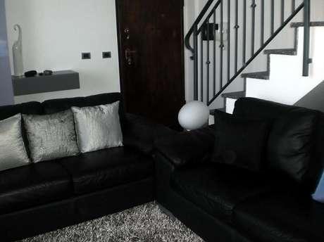 16. Dois conjuntos de sofá preto de 2 lugares complementam a decoração da sala. Projeto de Gabriele Barotto