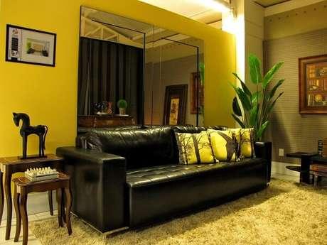 20. O sofá de couro preto equilibra o ambiente da sala com parede na cor amarela. Projeto de Symon Hilgemberg Santos