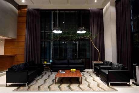 4. O sofá preto de couro se harmoniza com a tonalidade das cortinas. Projeto de Rafael Guimarães