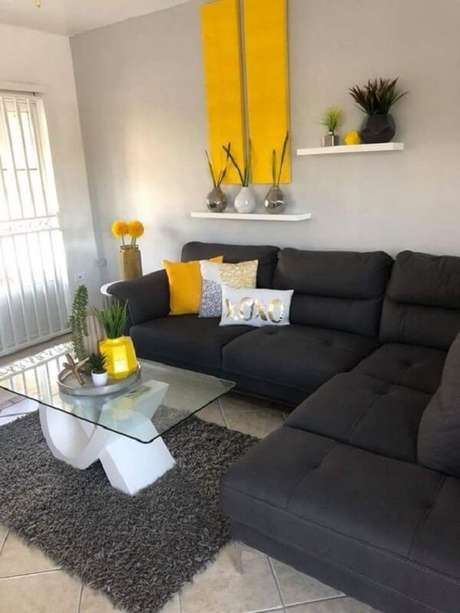 25. O sofá preto utilizado nesta sala neutraliza acessórios em tom amarelo. Fonte: Pinterest