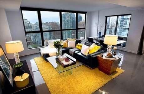 53. O tapete amarelo se harmoniza com o sofá preto. Fonte: Pinterest