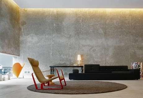 27. Paredes na cor concreto, sofá preto e tapete marrom complementam a decoração. Projeto de Studio MK27