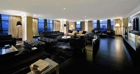 30. Sala ampla decorada com sofá 3 lugares preto. Projeto de Patricia Anastassiadis