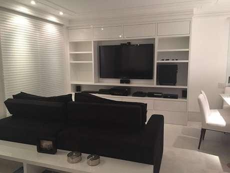 31. Sala de estar com móveis na cor branco e sofá preto de 2 lugares. Projeto de Cecilia Cruz