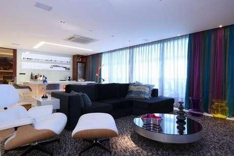 32. Sala de estar com sofá preto e poltrona branca. Projeto de Rodrigo Maia