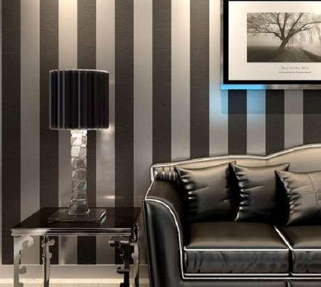 55. Sofá preto com papel de parede listrado transmite elegância. Fonte: Pinterest