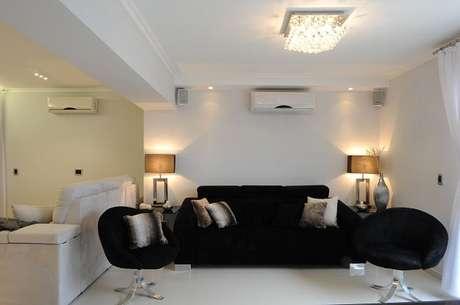44. Sofá preto e lustre com cristais complementam a decoração da sala. Projeto de Daniel Kalil