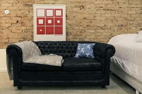 47. Sofá preto e parede de tijolinhos da sala de estar. Fonte: Casa Aberta
