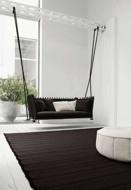 48. Sofá preto suspenso por cordas e uma viga de ferro no estilo namoradeira. Fonte: Pinterest