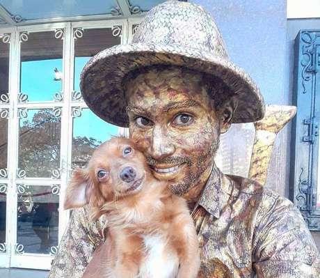 Yorge Luís Ruiz, artista de rua e imigrante venezuelano que trabalha como estátua viva em Fortaleza, Ceará, com sua cachorrinha.