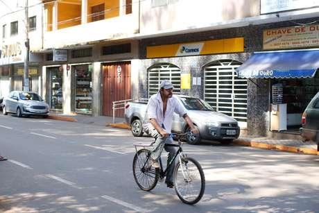 Homem pedala no centro de Barão de Cocais, em Minas Gerais, cidade onde o meio fio de algumas ruas foi pintado de laranja para sinalizar possível trajeto de rejeitos da barragem Sul Superior, da mineradora Vale