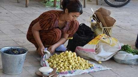 Vendedora de maçãs em Bukhara, vendendo uma variedade amarela cultivada no Uzbequistão