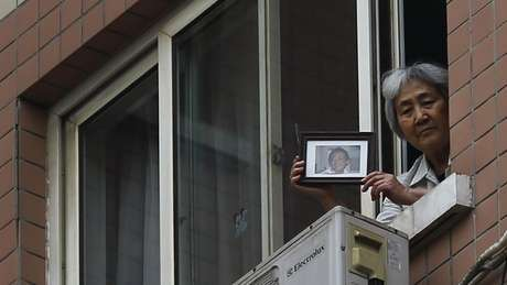Zhang Xianling mostra a jornalistas em 2014 uma foto do filho, vítima da repressão aos protestos