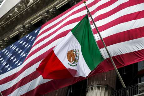 FILE PHOTO: The flag of Mexico changes in front of a large U.S. flag in front of the New York Stock Exchange September 4, 2015.  REUTERS/Lucas Jackson/File Photo