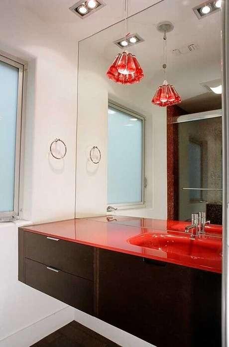 28. Decoração em tons de vermelho para banheiro com gabinete de madeira escura – Foto: Apartment Geeks