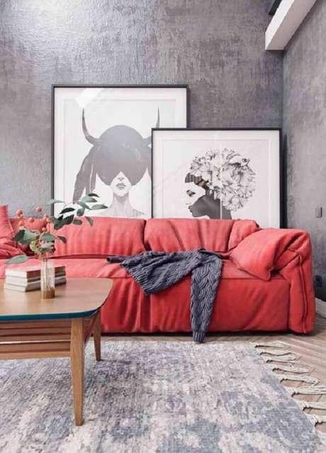 34. Decoração moderna para sala cinza com sofá vermelho e quadros apoiados no chão – Foto: Behance