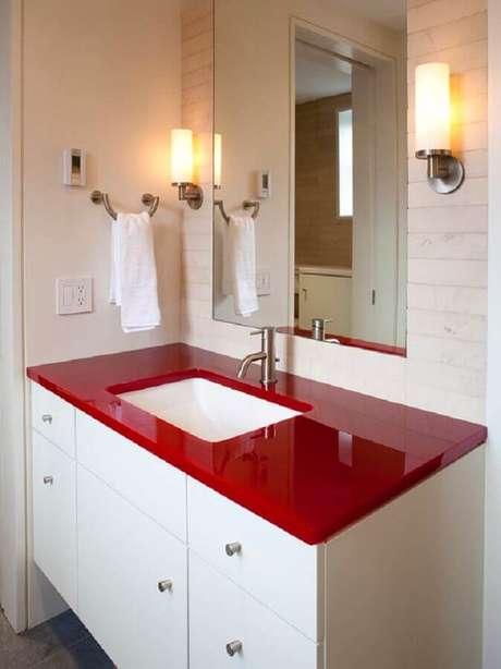36. Decoração para banheiro branco com bancada vermelha e arandela ao lado do espelho – Foto: Homedit