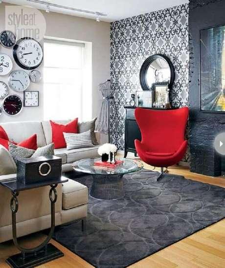 42. Decoração para sala em tons de vermelho e cinza com papel de parede e vários relógios – Foto: StyleAtHome