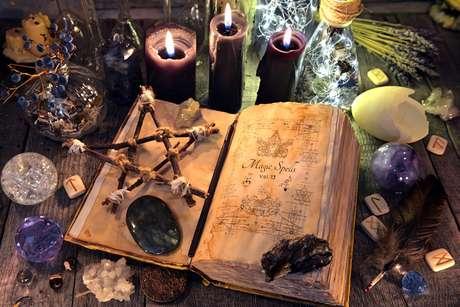 Antigo livro de bruxa com pentagrama, velas pretas, cristais e objetos rituais