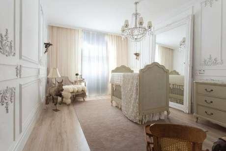 5. Quarto de bebê feminino de luxo clean, com espelho grande na decoração e cortinas em tons pasteis – Foto: Michele Luz