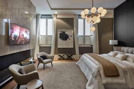 29. Quarto de luxo com televisão, lustre diferenciado e poltronas. – Foto: Casa Cor