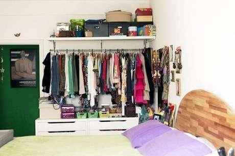 37. O closet aramado pode ser usado para complementar as cômodas de madeira no quarto.