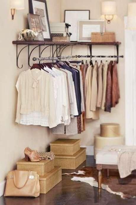 56. O closet aramado também fica lindo com prateleiras de quadros decorativos.