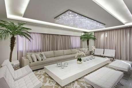 67. Sala de estar na cor cinza com lustre de cristal e cortinas claras – Foto: Arakilaris