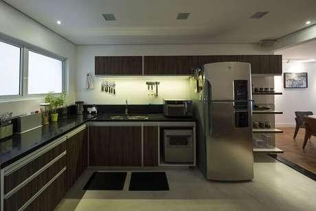 37. Armários de cozinha em l e bancada preta. Projeto de JAA Arquitetos