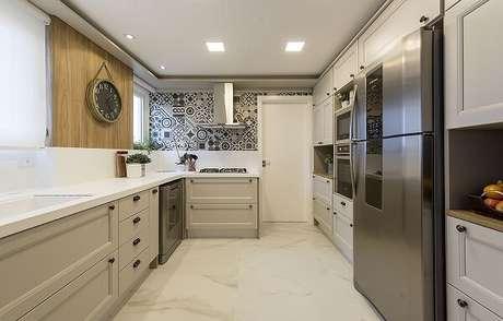 23. Cozinha em l com bancada e armários em tons de branco. Projeto de Espaço do Traço Arquitetura