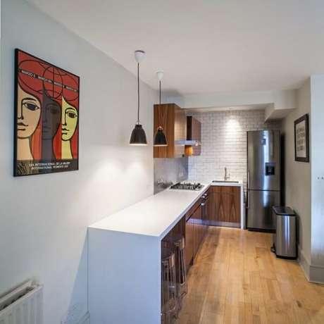 26. Cozinha em l pequena com bancada branca e cooktop embutido. Fonte: Arquidicas