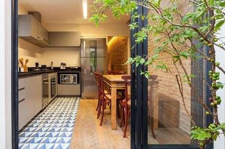 51. Cozinha planejada com parede de tijolinho vermelho. Projeto de Tria Arquitetura