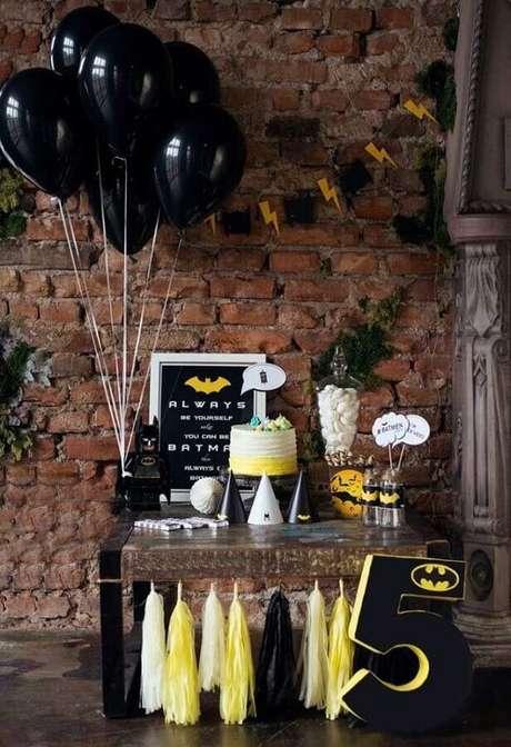 30. A parede de tijolinho deu um toque aconchegante na decoração do Batman para festa infantil – Foto: Pinosy