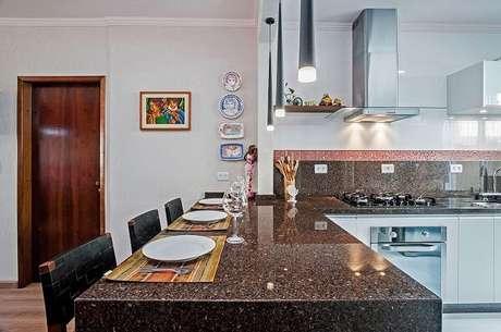 55. Pendentes e quadros decorativos enfeitam a cozinha em l com bancada. Projeto de Patrícia Azoni