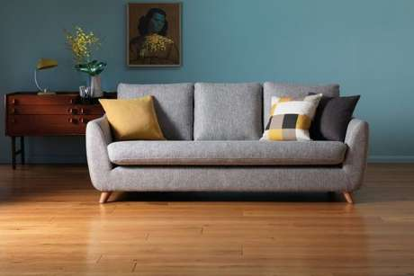 11. Sofá retrô na cor cinza com almofadas neutras e parede azul – Foto: G Plan Vintage