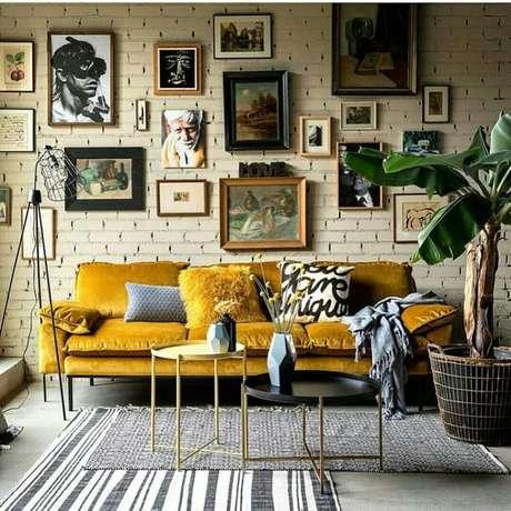 4. Sofá retrô mostarda com decoração moderna cheia de quadros – Foto: Tabara Home