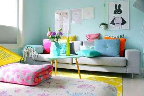 28. Para quem gosta de ambientes coloridos, aposte no sofá retrô cinza e use tapetes e almofadas divertidas para conseguir uma decoração alegre. – Foto: Pinterest