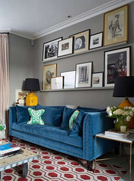 31. Decoração de sala com sofá retrô azul e muitos quadros, perfeito para salas modernas. – Foto:Pinterest