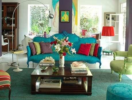 27. Use almofadas coloridas e flores como decoração para ter uma sala alegre e divertida junto do sofá retrô. – Foto: Pinterest