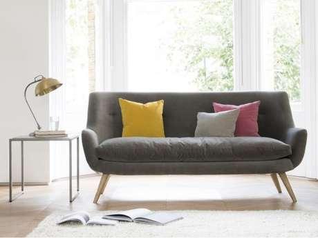 45. Os tons de amarelo e rosa combinam com o sofá retrô cinza. Aposte nelas! – Foto: Architectual Design