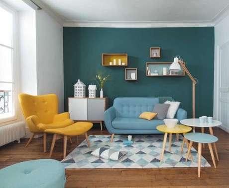 17. Sala com sofá retrô azul e detalhes como poltrona em amarelo – Foto: Pinterest