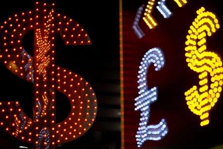 Símbolos de várias moedas são vistos na frente de uma casa de câmbio em Hong Kong.  1/11/2014.  REUTERS/File Photo