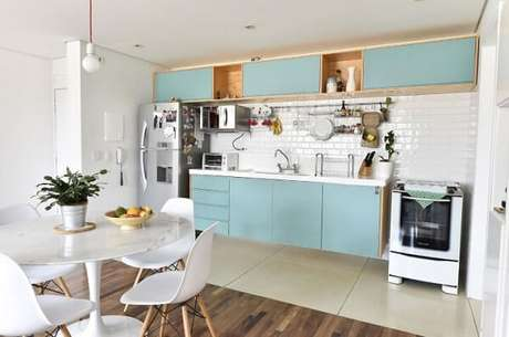 18. Cozinha integrada com armários em azul claro. Projeto de Carla Cuono
