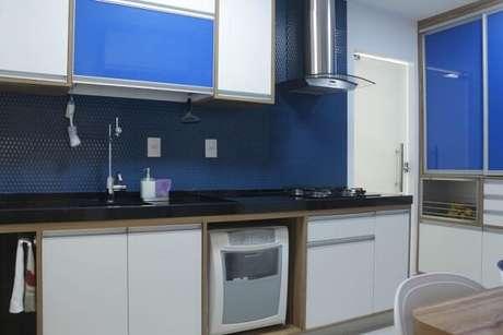 20. Cozinha planejada com parede e móveis em tons de azul e branco. Projeto de Espaço AU