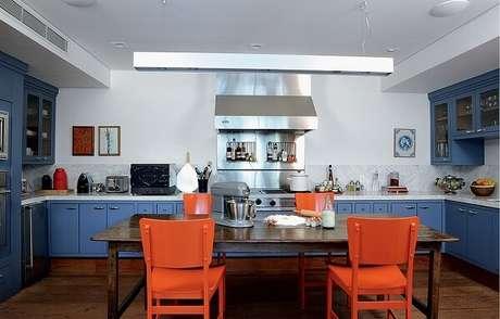 58. Mescle tonalidades incluindo no ambiente, armários na cor azul e cadeiras na cor laranja. Fonte: Casa e Jardim