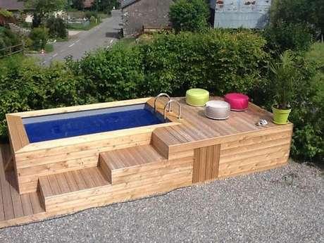 38. Caso não tenha espaço para espreguiçadeiras, use puffs coloridos para decorar sua piscina de paletes. Fica incrível!