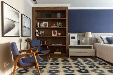 27. Quarto de casal com parede em tons de azul combinando com as poltronas, tapete e roupas de cama. Projeto de Marilia Veiga