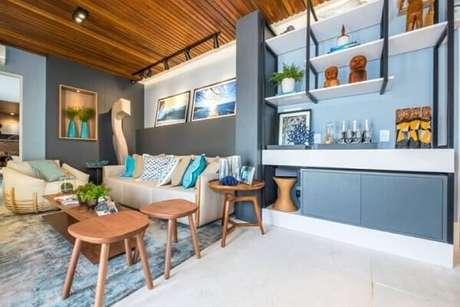 41. Sala de estar com parede, tapete, armários e objetos de decoração em tons de azul. Projeto de Casa Cor Rio Grande do Norte
