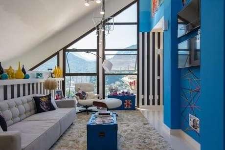 42. Sala de TV com parede e móveisem tons de azul. Projeto de MMPM