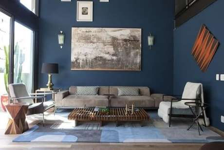 7. Como a sala é bem iluminada, as paredes em tons de azul escuro trouxe personalidade ao ambiente. Projeto de AMC Arquitetura
